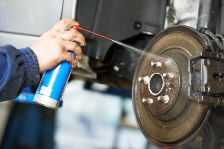 auto monteur: automonteur reinigen van auto wiel remschijf tegen roest corrosie bij auto-reparatie tankstation Stockfoto
