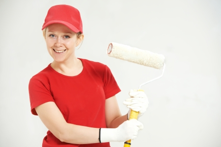 prime adult: Smiling female house painter worker with painting roller