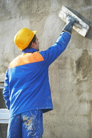 builder at facade plastering work during industrial building with putty knife float photo