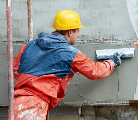 parget: Facade Plasterer builder working at outdoor wall renovation decoration with float Stock Photo