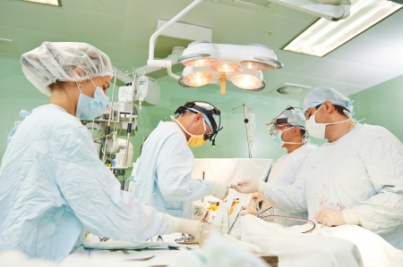 physicals: Team of surgeon in uniform perform operation on a patient at cardiac surgery clinic Stock Photo