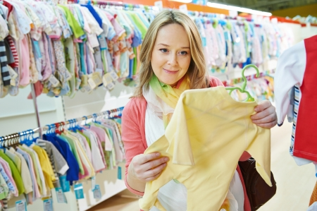 clothing stores: Young pregnant woman choosing newborn clothes at baby shop store Stock Photo