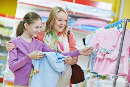 kids wear: pregnant woman and little girl choosing newborn baby clothes during shopping at garments supermarket Stock Photo