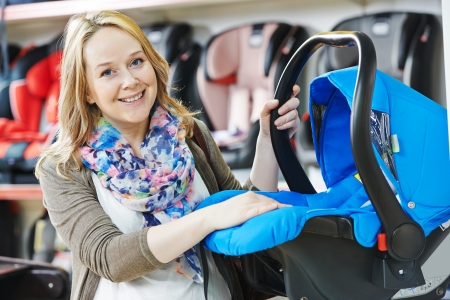 sales assistant: woman choosing child car seat for newborn baby in shop supermarket Stock Photo