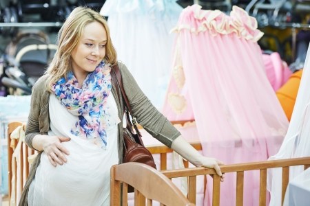 bassinet: Young pregnant woman choosing cot or bassinet for newborn baby at infant shop Stock Photo