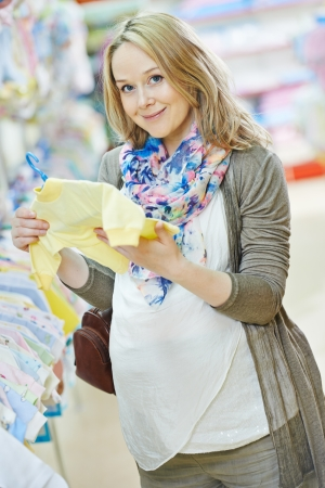 choosing clothes: Young pregnant woman choosing newborn clothes at baby shop store Stock Photo