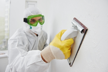 home improvement: Home improvement worker in protective mask and glasses working with sander for smoothing wall surface