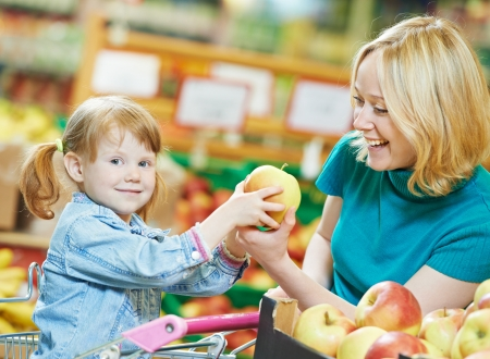 woman and little girl choosing apple during shopping at fruit vegetable supermarket Stock Photo - 24207825