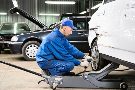 lifting jack: mechanic matching automobile headlight lamp to damaged car at repair service station Stock Photo