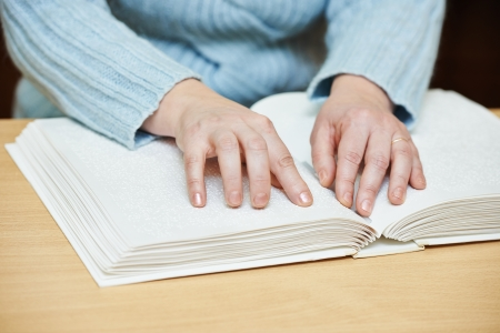 visually: Blind or visually handicapped woman hands reading book written in Braille
