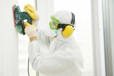 respirator: Home improvement worker in protective mask and glasses working with sander for smoothing wall surface