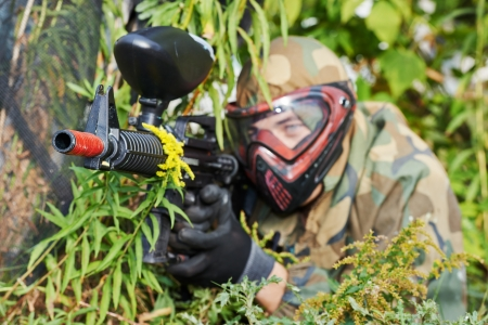Adrenalin paintball player in protective uniform and mask aiming gun before shooting in summer photo