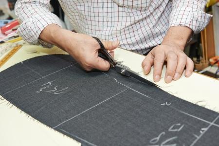 Tailor Hände Arbeit mit Schere und Anzug Textiltuch Standard-Bild