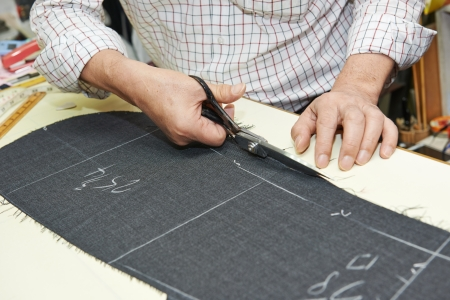 tailor shop: Tailor hands working with scissor and suit textile cloth