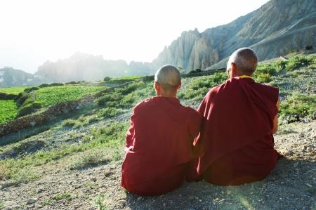 Twee Indiase Tibetaanse oude monniken lama in rode kleur kleding zitten in de voorkant van de bergen