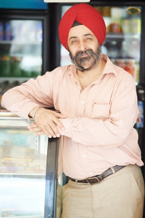 sikh: Portrait of Indian sikh man seller in turban with bushy beard at shop Stock Photo