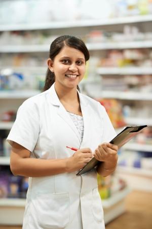 cheerful pharmacist chemist woman standing in pharmacy drugstore photo