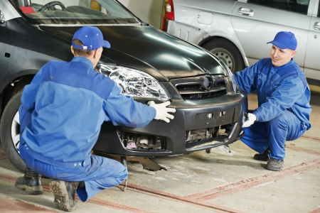 two car garage: Two repairman mechanics matching automobile body bumper on damaged car at repair service station Stock Photo