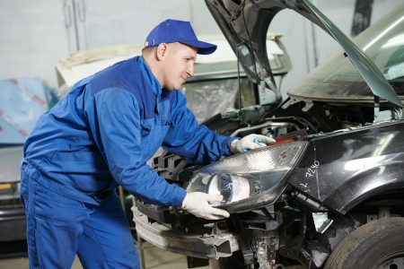 bodywork: mechanic matching automobile headlight lamp to damaged car at repair service station Stock Photo