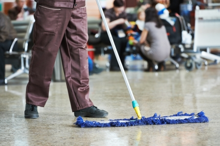 dweilen: reiniger met mop en uniforme reinigen vloer in de hal van de publieke zaak, gebouw