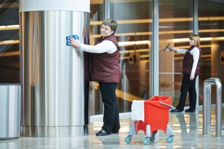 cleaning team: dos trabajadores m�s limpia mujer en uniforme de limpieza indoor interior del edificio de negocios