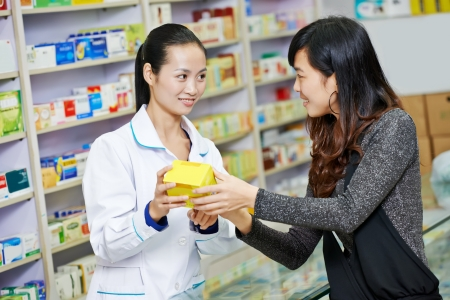 Two cheerful chinese pharmacist chemist woman standing in china pharmacy drugstore photo