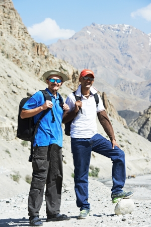 travel guide: happy smiling tourist traveller hikers in india Himalayas mountains Stock Photo