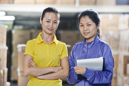 warehousing: two young chinese female workers in uniform at warehousing system