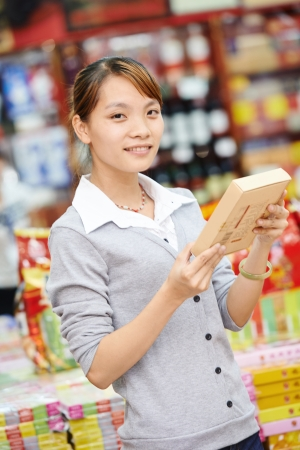 chinese young woman choosing food tea during shopping at china supermarket photo