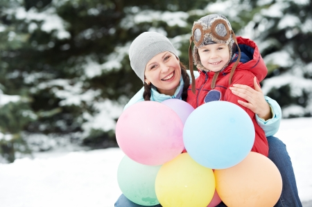 Portrait of happy mother with little child son boy and in winter outdoors photo
