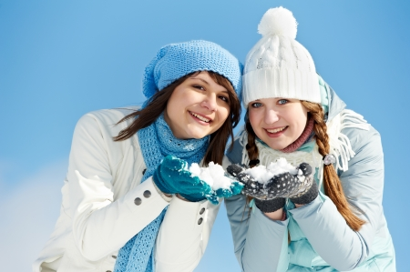 Two girl having fun with snow in winter outdoors photo