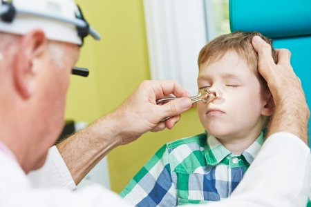 Medical otolaryngologist ear nose throat doctor rinsing nose at boy child Imagens - 24300269