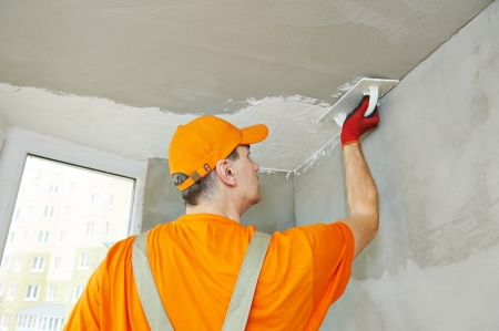 Plasterer at indoor ceiling renovation decoration with float and plaster photo