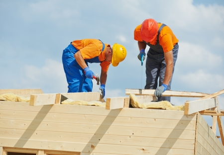 Two construction carpenters roofers workers installing wood board roof Stock Photo