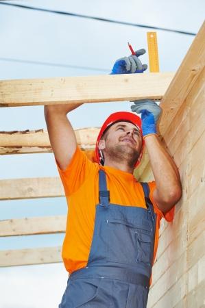 trussing: carpentiere operaio di misura tavola di legno con un angolo sul lavoro di installazione sul tetto Archivio Fotografico