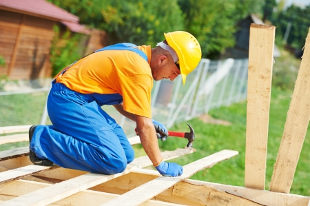 construction roofer carpenter worker hammering wood board with hammer and nail on roof installation work photo