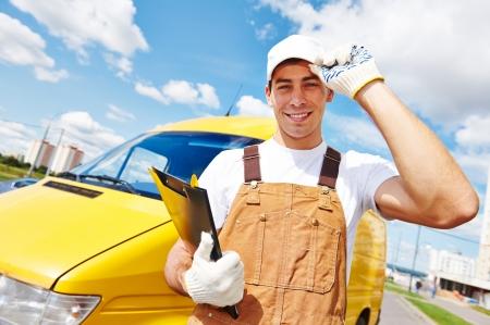 Lachende jonge mannelijke leveringskoerier man voor bestelwagen voor het leveren of verhuizing