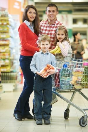 carro supermercado: mujer con el hombre y el ni�o con cortar la compra durante las compras en el supermercado vegetal