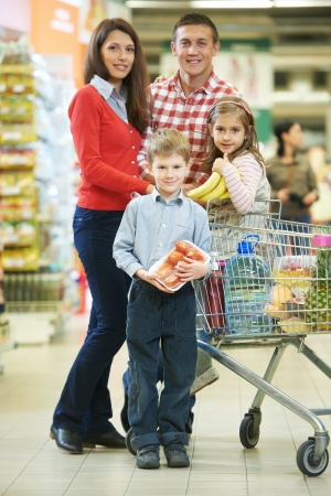 woman with man and child with chopping cart during shopping at vegetable supermarket photo