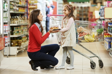 grocery shopping: woman and little girl choosing apple during shopping at fruit vegetable supermarket Stock Photo