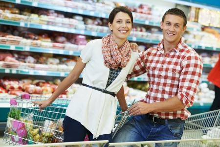 Young Family couple choosing bio food in grocery supermarket during weekly shopping photo