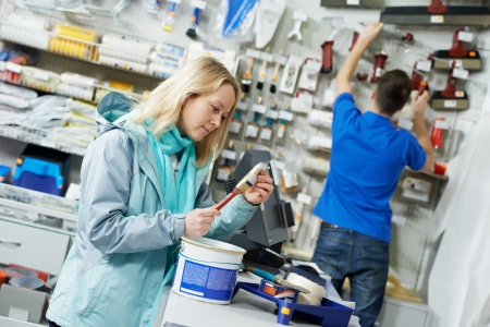 Purchaser woman choosing paintbrush for painting at hardware store