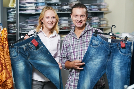 Young couple choosing jeans during clothing shopping at sales store photo