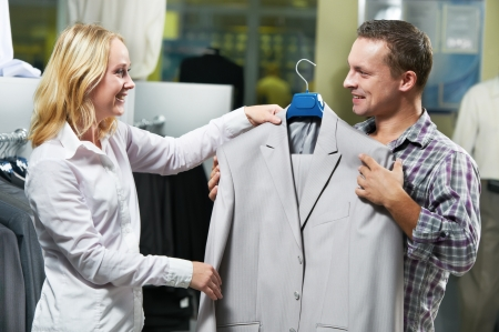 Young couple choosing business suit shirt and necktie during clothing shopping at sales store photo