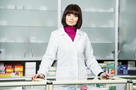 cheerful pharmacist chemist woman standing in pharmacy drugstore photo