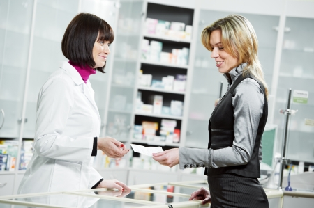 pharmacist suggesting medical drug to buyer in pharmacy drugstore photo