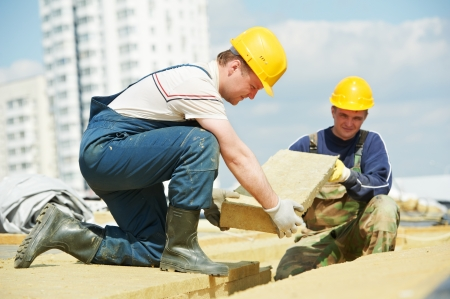 roofing membrane: Roofer builder worker installing roof insulation material Stock Photo