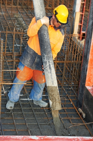builder worker standing near trailer-mounted boom concrete pump on metal rods reinforcement of concrete casting formwork Stock Photo - 24711603