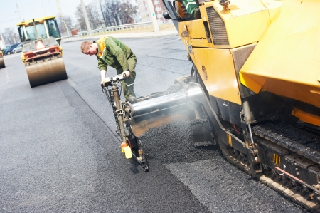 Worker operating asphalt paver machine during road construction and repairing works 免版税图像
