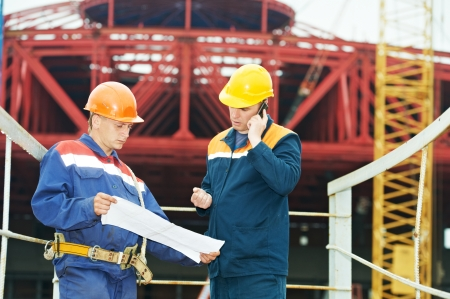 foremaster: Two engineer builders with blueprint plan at construction site Stock Photo